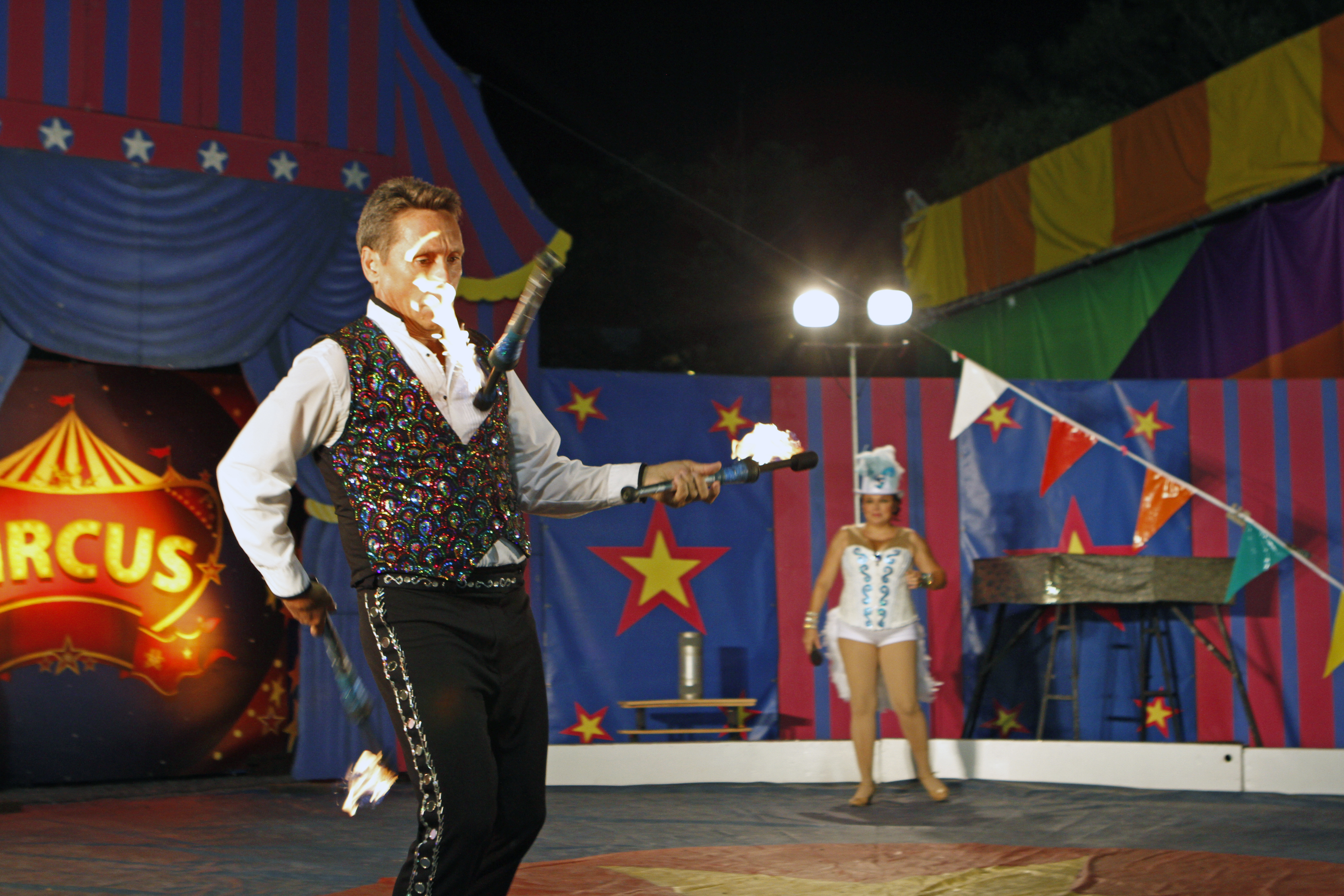 a man juggling flame lit torches in a circus setting at night