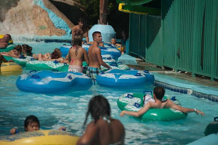 people floating down a lazy river in colorful intertubes on a hut summer day