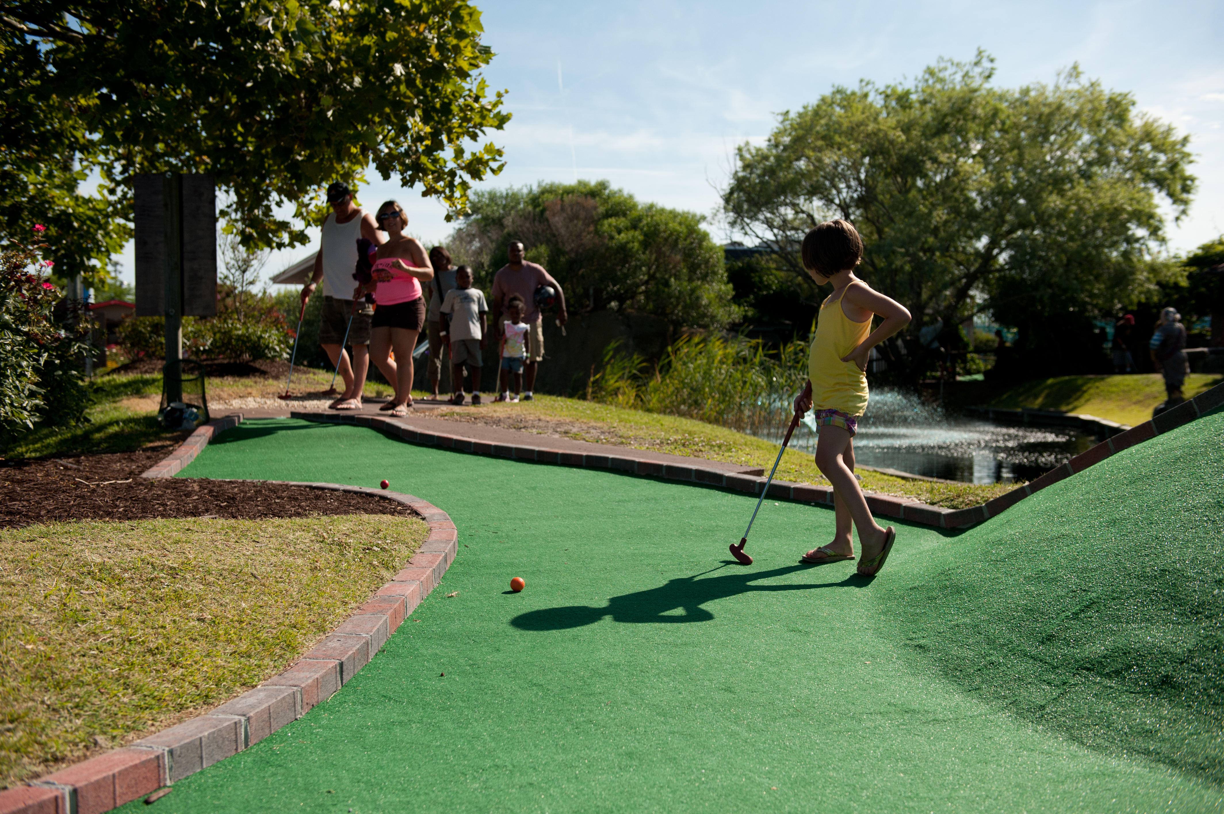 a young girl with short dark hair playing miniature golf with her parents