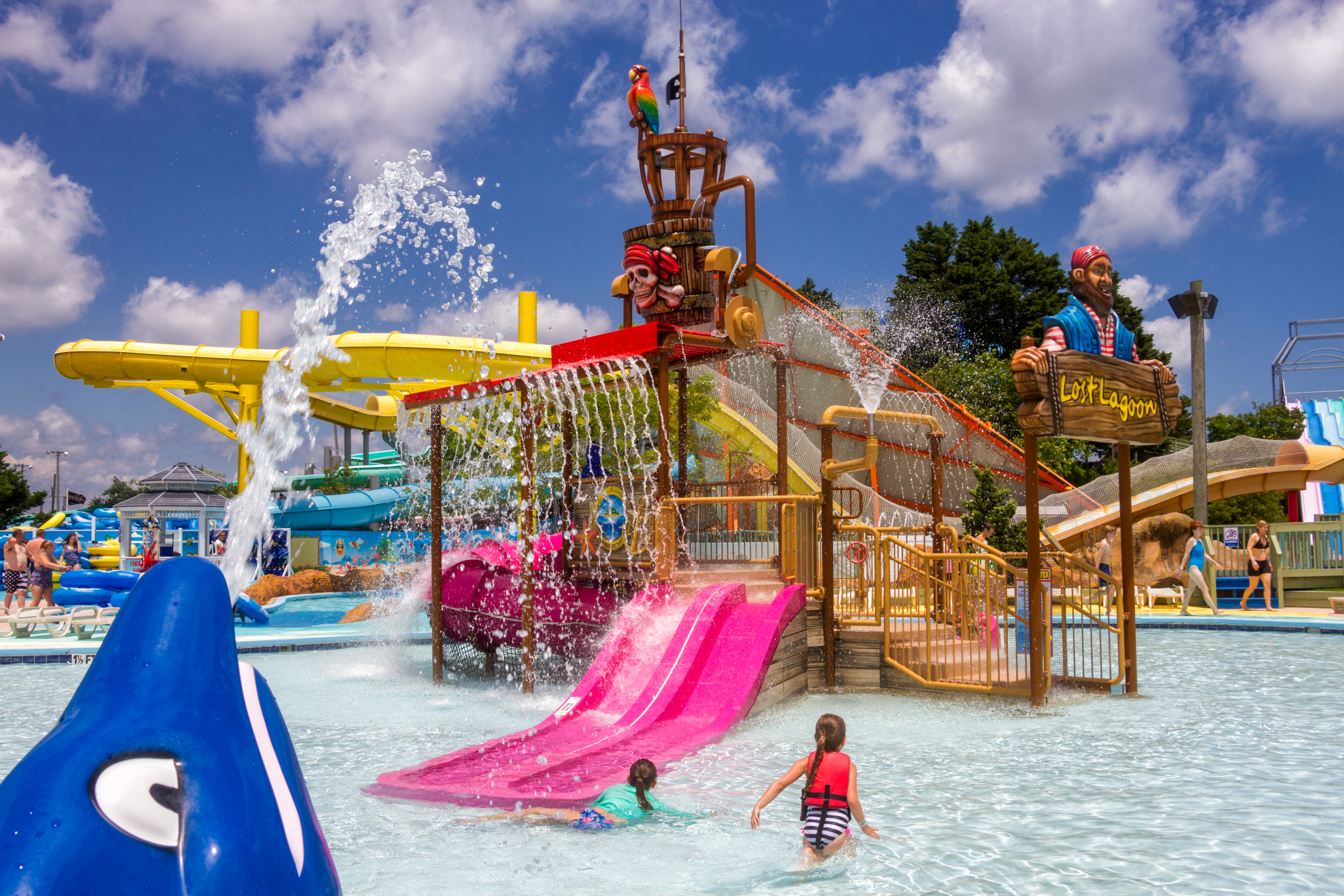 a childrens play area in a water park on a bright sunny day