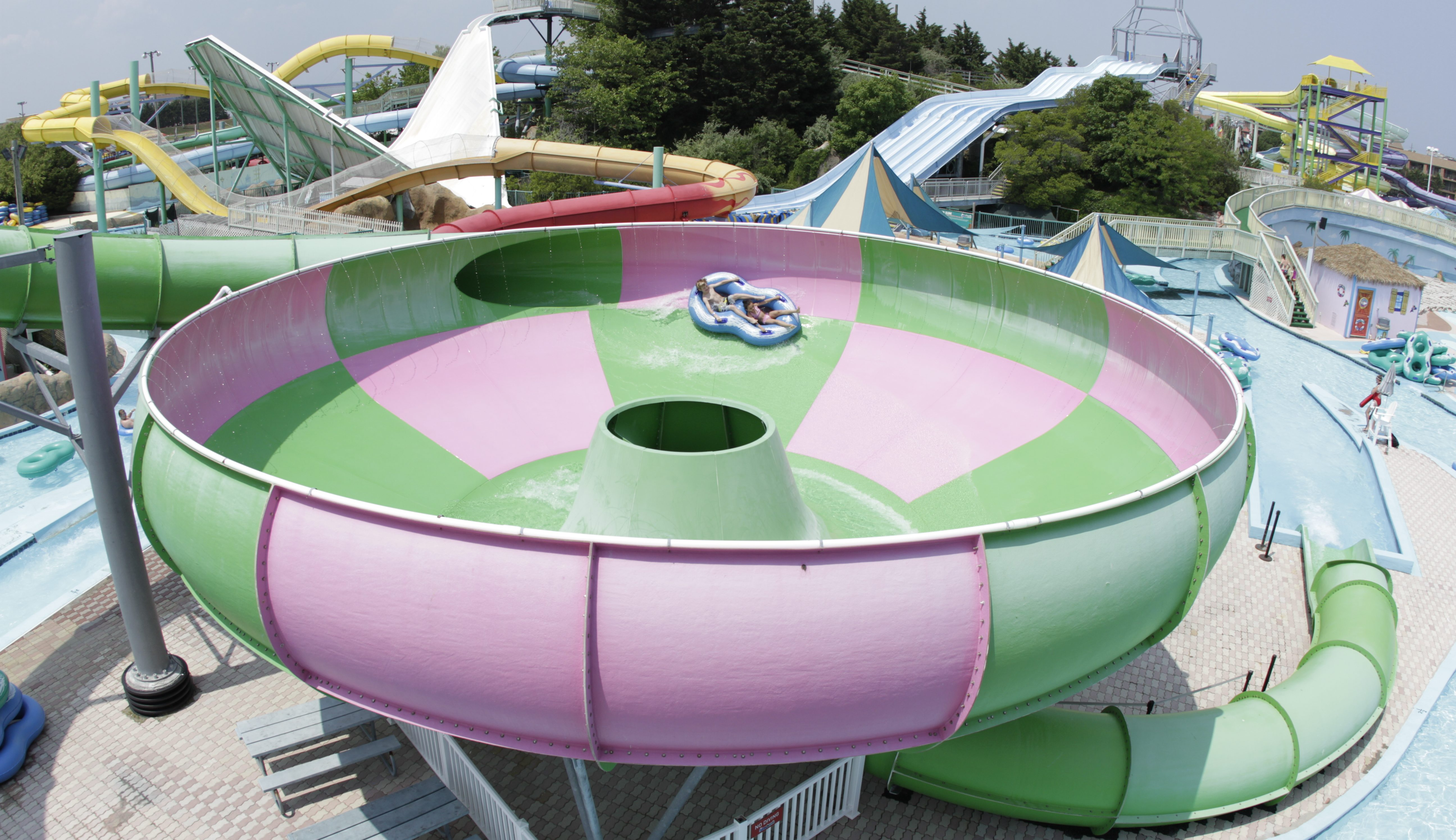 a pink and green hurricane shaped ride at a water park