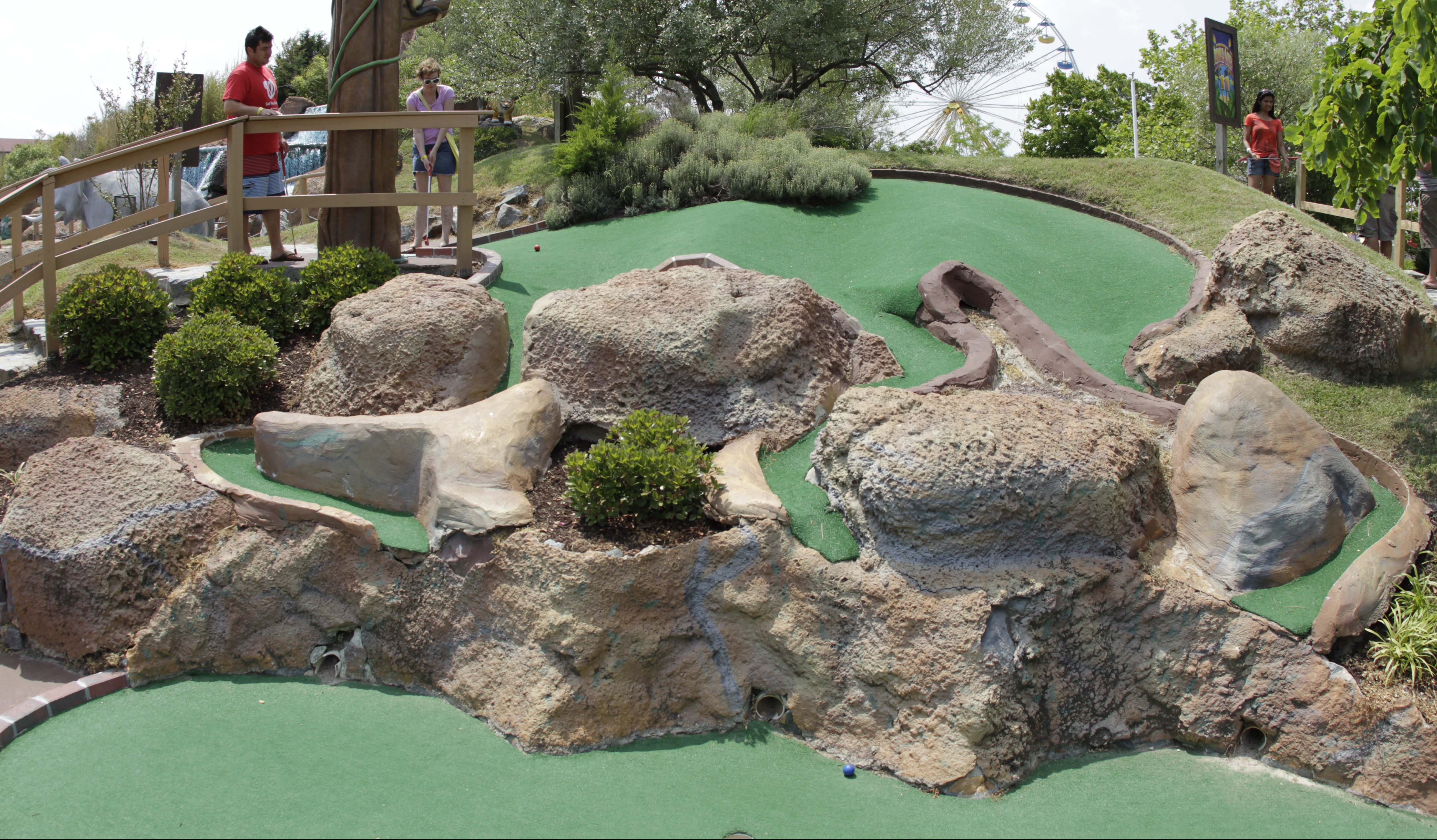 green turf grass on a miniature golf course with boulders and rope walk